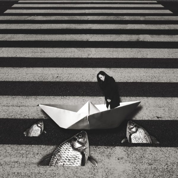 A surrealistic image: on a crosswalk, there is a paper boat, fish coming our of the tarmac and a lady looking down.